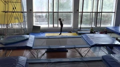 Stock Video Footage of Young girl gymnast warm up in the gym on a trampoline, top view