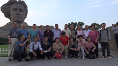 Chinese tourists pose in front of Mao Zedong statue in Changsha Stock Footage