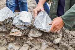 hands working on masonry stone wall - stock photo