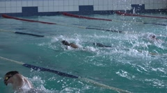 Young swimmers swimming competitions in the pool, water, spray Stock Footage