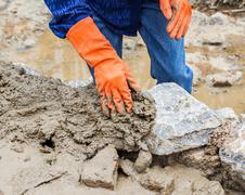 Hands working on masonry stone wall Stock Photos
