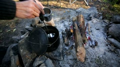 Woman pouring tea from a kettle after preparing on a bonfire. Stock Footage