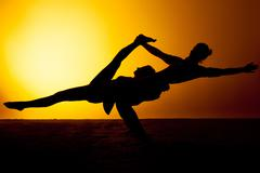 Two people practicing yoga in the sunset light - stock photo