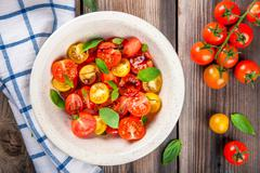 Salad of organic cherry tomatoes with basil, balsamic and olive oil Stock Photos