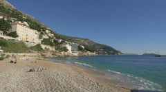 People tanning and relaxing on the Old Town Beach in Dubrovnik - stock footage