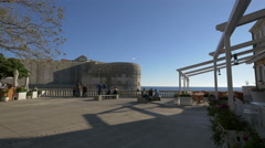 People sitting on benches on a terrace near the sea in Dubrovnik Stock Footage