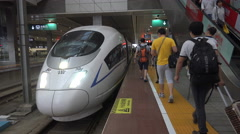 Passengers walk towards a high speed (bullet) train in Changsha, China Stock Footage