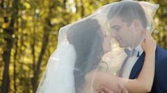 Bride and groom walking in park, kissing Stock Footage