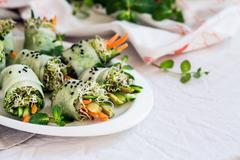 Raw vegan rolls with sprouted seeds and carrots - stock photo