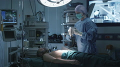 Medical Team Performing Defibrillation in Modern Operating Room Stock Footage