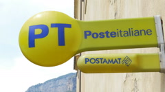 Yellow Poste Italiane sign outside store. Stock Footage