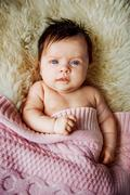 newborn baby lying with open eyes in crib - stock photo