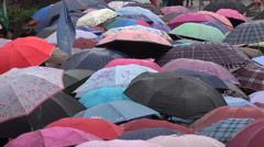Abstract view of Chinese tourists holding umbrella in the rain Stock Footage