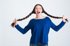 Amusing pretty woman holding her two long braids and shouting - stock photo