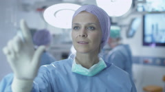 Nurse using Imaginary Futuristic Analytical Interface in Operating Room Stock Footage