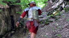 Stock Video Footage of Roman soldier on a slope uphill run to hide in the woods and escape pursuers