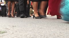 Column of people marching in a concrete way, following the two grooms Stock Footage