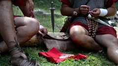 Roman soldiers sitting on a trunk felled in the forest and eat out of a piece Stock Footage