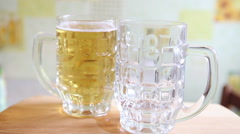 The beer is poured from a glass bottle into a large mug Stock Footage