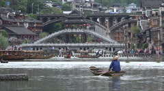 China, worker paddling through Fenghuang, keeping the village clean Stock Footage