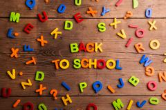 Colorful plastic letters, numbers, back to school,  wooden backg - stock photo