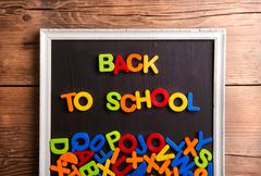 Colorful plastic letters in picture frame, back to school - stock photo