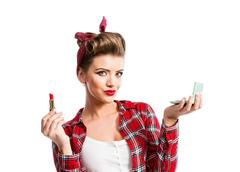 Woman with pin-up hairstyle holding mirror, applying red lipstic Stock Photos