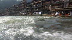 Tourist boats in a small current in Fenghuang, China Stock Footage