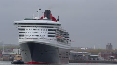 Stock Video Footage of Cunard cruise liner 'Queen Mary 2', is manoeuvred by tug