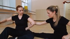 Two women, dancers in black clothes come up with a new dance. on the floor. Stock Footage