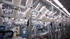 Worker at three dimensional knitting machines in a factory of knitted underwear. - stock footage
