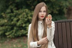 beautiful blonde woman with extra long straight hair on park bench - stock photo