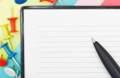 Notepad with pen and pushpins - stock photo