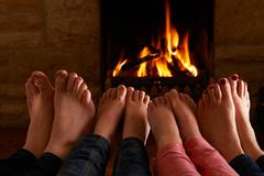 Family Warming Feet By Fire - stock photo