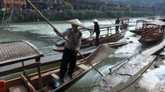 Workers push rowing boats upstream in popular Fenghuang town, China - stock footage