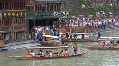 Chinese tourists queue for a popular trip with wooden rowing boats in Fenghuang Stock Footage