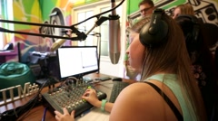 """Oung woman dj work in front of a microphone on """"Play FM"""" radio. Stock Footage"""