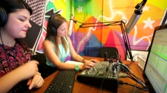 "Young woman dj work in front of a microphone on ""Play FM"" radio. Stock Footage"