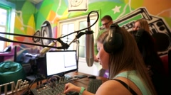 """Young woman dj work in front of a microphone on """"Play FM"""" radio. - stock footage"""