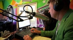 """Dj man work in front of a microphone on """"Play FM"""" radio. Stock Footage"""
