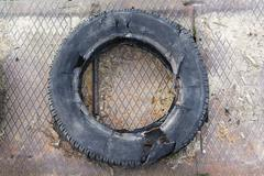 Deteriorated abandoned tire - stock photo