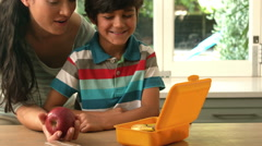 Happy mother putting apple in her sons lunch box Stock Footage