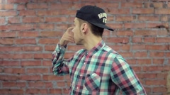 Boy in cap, plaid shirt try start monologue on camera. Brick wall on background Stock Footage