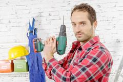 Young carpenter holding a drill as a weapon Stock Photos