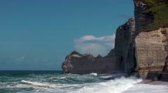 Cliffs waves white caps foam blue sky - stock footage