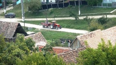 Tractor which has in the trailer a man with a shovel goes on the central street Stock Footage