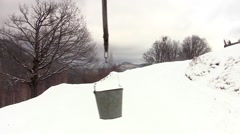 Metal bucket swinging in the wind above a snow-covered fountains Stock Footage