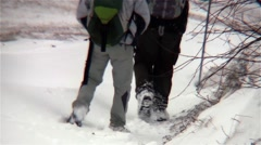 Tourists with backpack behind down a road covered in snow, rushing to a cottage Stock Footage