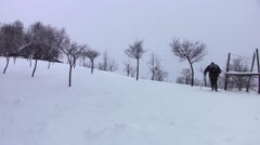Tourists who go backpacking climb a snowy slope through a deserted orchard Stock Footage