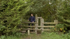 Hiker Walking Over Stile In Autumnal Wood Stock Footage